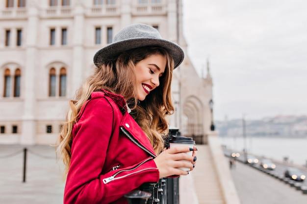 Śliczna kobieta w szarym kapeluszu, śmiejąca się z zamkniętymi oczami w zimny wiosenny poranek