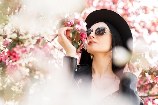 Śliczna kobieta w ukwieconym parku spaceruje po przyrodzie. urocza dziewczyna w eleganckim kapeluszu w modnych okularach przeciwsłonecznych w czarnym modnym stroju i różowe wiosenne kwiaty na zewnątrz. piękna pani wącha niesamowite kwitnące drzewo.