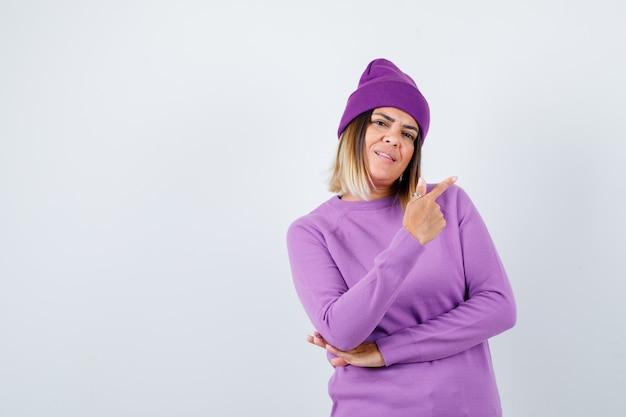 Śliczna kobieta, wskazując na prawy górny róg w swetrze, czapce i wyglądającym pewnie. przedni widok.