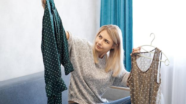 Śliczna kobieta wybiera swój strój, trzymając dwie sukienki na wieszakach