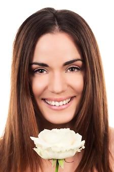 Śliczna kobieta z białą różą w studio