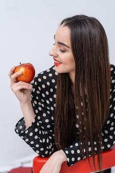 Śliczna kobieta z czerwonymi ustami. kobieta patrząc na jabłko w dłoniach. wyrazy twarzy.