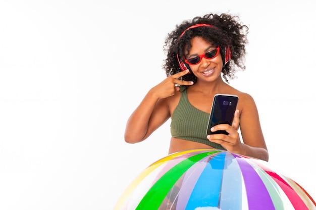 Śliczna kobieta z dużymi czerwonymi słuchawkami, okularami przeciwsłonecznymi i telefonów stojakami z dużą gumową piłką na bielu