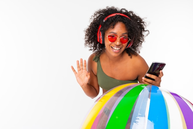 Śliczna kobieta z dużymi czerwonymi słuchawkami, okularami przeciwsłonecznymi i telefonów stojakami z dużą gumową piłką odizolowywającą na bielu