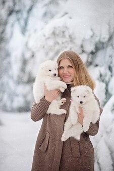 Śliczna kobieta z dwoma puszystymi białymi psami w zimowym lesie