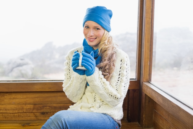 Śliczna kobieta z filiżanki obsiadaniem w ciepłej odzieży przeciw okno