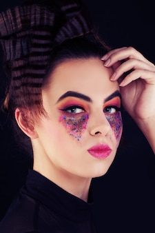 Śliczna kobieta z kolorowym makijażem. kreatywny makijaż i fryzura