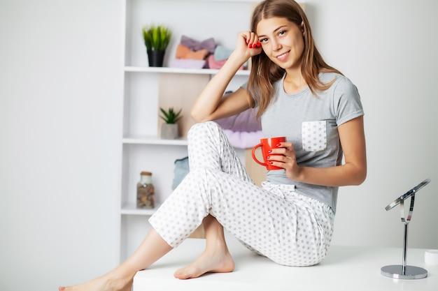 Śliczna kobieta z pięknym uśmiechem w nowych piżamach przygotowywa dla łóżka