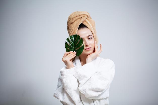 Śliczna kobieta z ręcznikiem na głowie i zielonym liściem po wzięciu prysznica