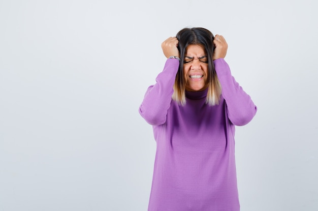 Śliczna kobieta z rękami na głowie w fioletowym swetrze i wygląda na zirytowaną. przedni widok.