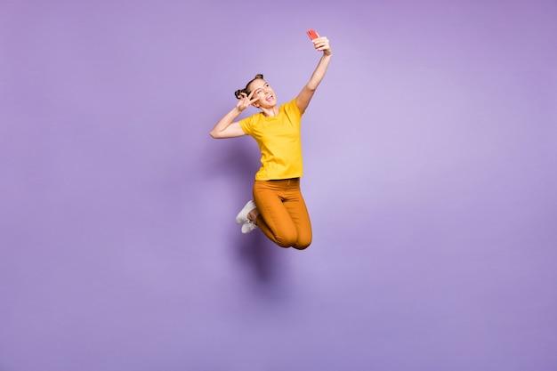 Śliczna kobieta z topknotami, pozowanie na fioletowej ścianie