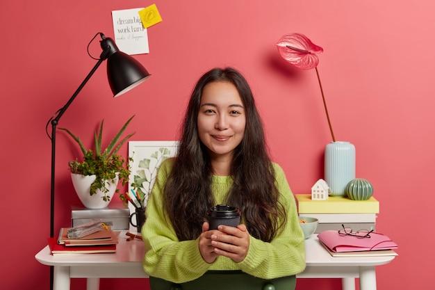 Śliczna koreańska uczona w zielonym swetrze, trzyma filiżankę kawy na wynos, przygotowuje badania w domu, pozuje przeciwko przytulnemu miejscu pracy z kwiatami