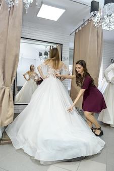 Śliczna krawiecka mierzy długość sukni ślubnej