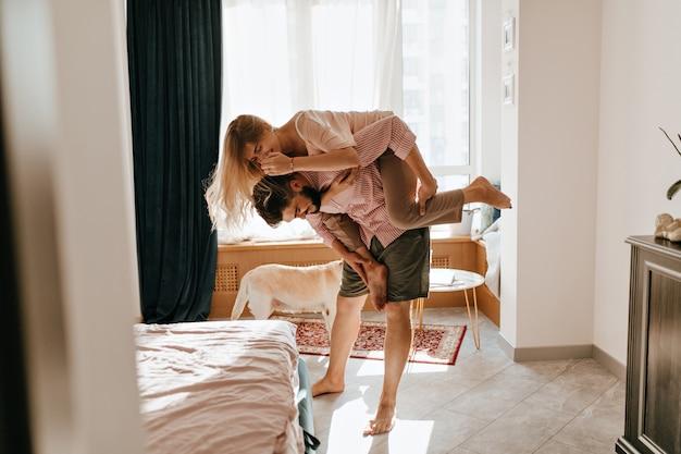 Śliczna kręcona dziewczyna wskoczyła na plecy chłopaka. historia miłosna pary podrywającej się w przytulnym przestronnym pokoju.