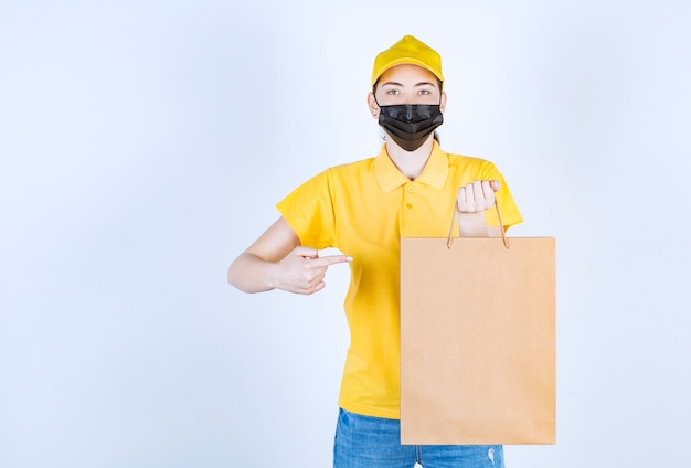 Śliczna kurierka w żółtej czapce wskazuje torbę palcem, który trzyma w lewej ręce przed białą ścianą
