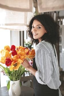 Śliczna kwiaciarka w fartuchu tworząca piękny bukiet kolorowych kwiatów. młoda african american girl z ciemnymi kręconymi włosami stojącej z tulipanów