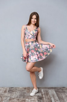 Śliczna ładna beztroska dziewczyna w kwiecistej bluzce i spódnicy i trampkach na szarej ścianie