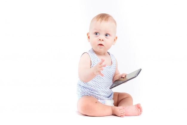 Śliczna ładna chłopiec w błękitnej koszula i pieluszka trzymamy telefon komórkowego