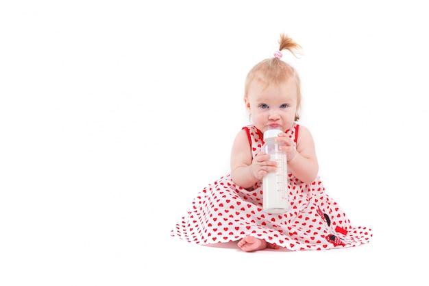 Śliczna ładna mała dziewczynka w czerwonej sukni z butelką mleka