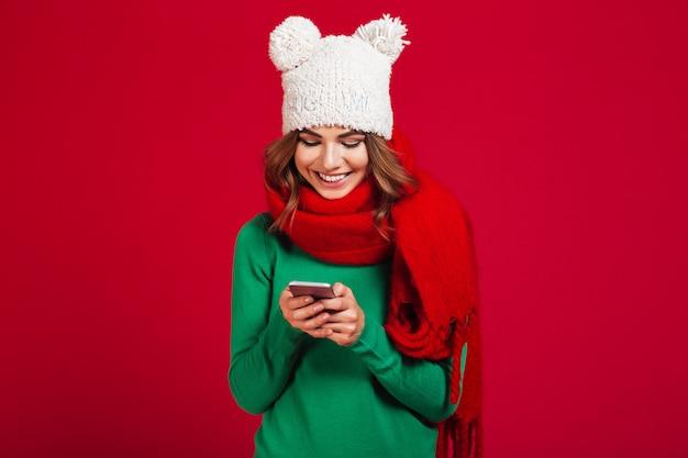 Śliczna ładna młoda kobieta jest ubranym kapelusz i szalika.