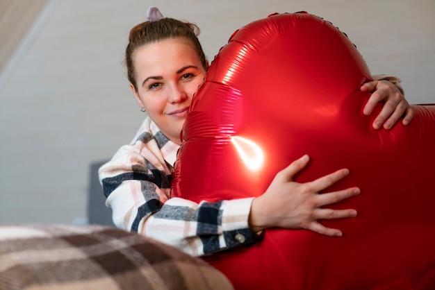 Śliczna ładna młoda kobieta, piękna dziewczyna z dużym czerwonym balonem w kształcie serca siedzi na łóżku o godz