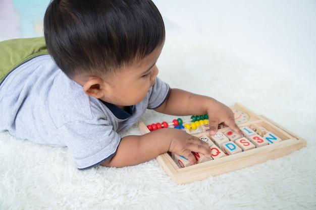 Śliczna mała asin chłopiec bawić się z drewnianą zabawką