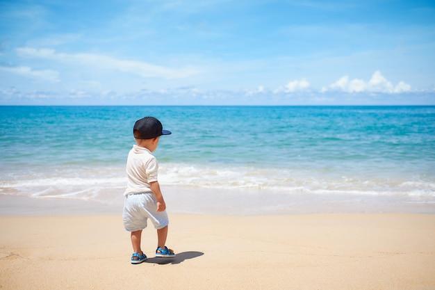 Śliczna mała azjatycka berbeć chłopiec pozycja, odprowadzenie, bawić się na pięknej piaskowatej tropikalnej plaży w wakacje