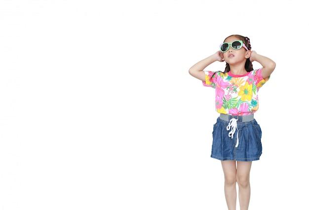 Śliczna mała azjatycka dzieciak dziewczyna jest ubranym kwiaty lata suknię i okulary przeciwsłonecznych odizolowywających. gotowy na letnie wakacje.