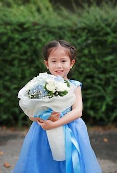 Śliczna mała azjatycka dziecko dziewczyna z bukietem kwiaty w ogródzie
