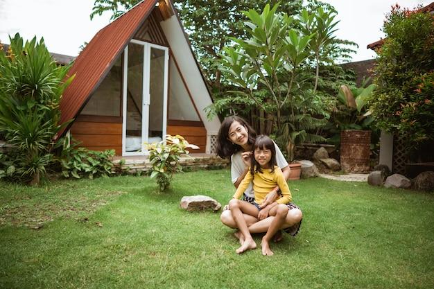 Śliczna mała azjatycka dziewczyna pomaga swojej matce bawić się i bawić na podwórku.