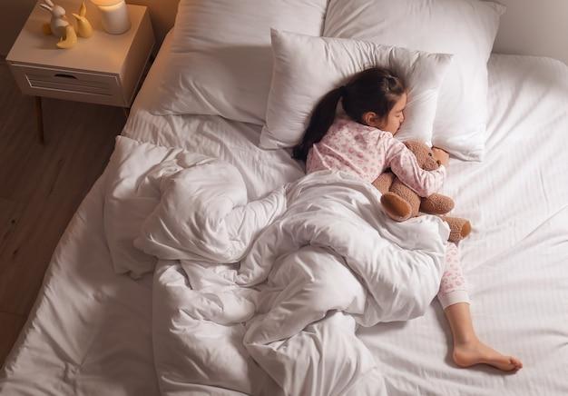 Śliczna mała azjatycka dziewczyna śpi w łóżku