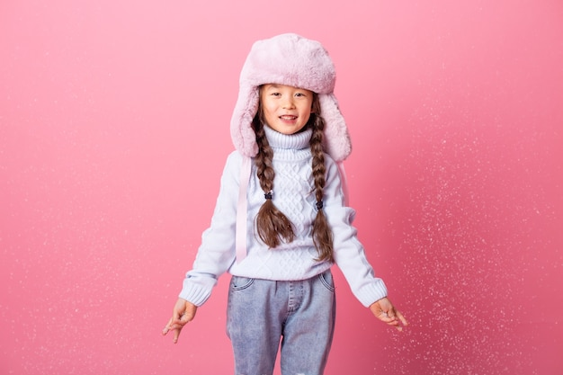 Śliczna mała azjatycka dziewczyna w zimowe ubrania wieje śnieg z dłoni. koniec zimy, różowe tło, miejsce na tekst