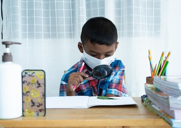 Śliczna mała azjatykcia chłopiec uczy się online z smartphone w domu