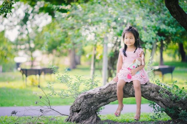 Śliczna mała azjatykcia dziewczyna z lali obsiadaniem w parku