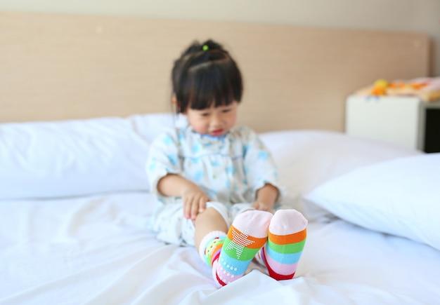 Śliczna mała azjatykcia dziewczyny odzież skarpety na łóżku.