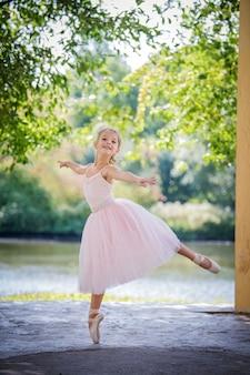 Śliczna mała balerina w różowej sukience latem na zewnątrz