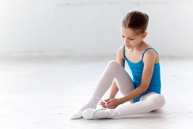 Śliczna mała baletnica w niebieskiej sukience do tańca zakładająca pointe