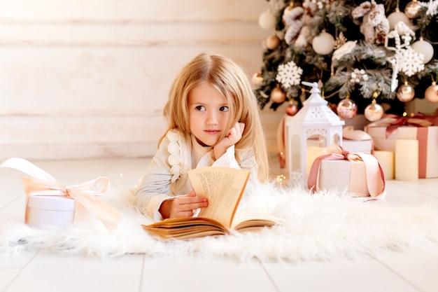 Śliczna mała blondynka czyta książkę w domu w pobliżu choinki