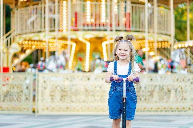 Śliczna mała blondynka w parku rozrywki