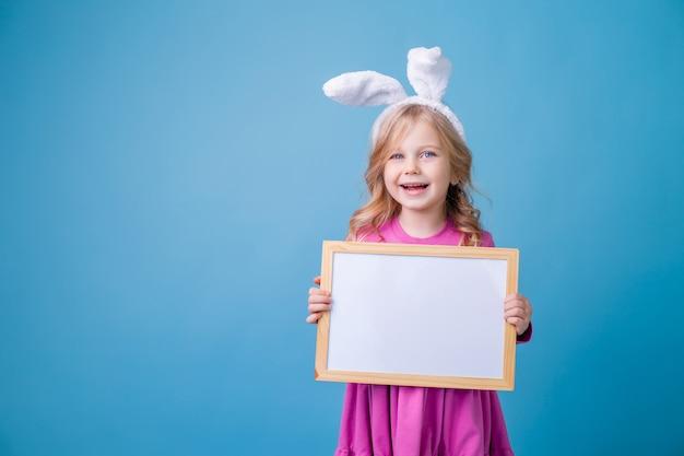 Śliczna mała blondynka w uszach zajączka wielkanocnego trzymającego białą pustą tablicę ogłoszeń.