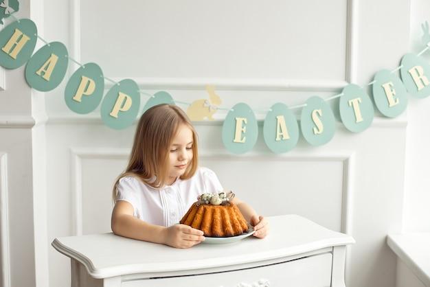 Śliczna mała blondynki dziewczyna siedzi przy białym rocznika stołem i patrzeje smakowitego ciasto