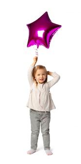 Śliczna mała blondynki dziewczyna z purpury gwiazdą kształtował baloon odizolowywającego na białym tle