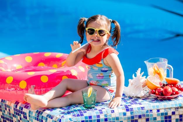 Śliczna mała brunetka dziewczyna w okularach przeciwsłonecznych i kostiumie kąpielowym pije lemoniadę przy basenie.