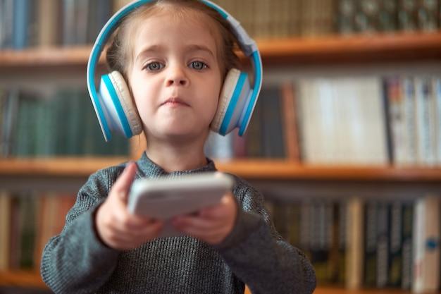 Śliczna mała caucasian dziewczyna z hełmofonami i smartphone salowymi