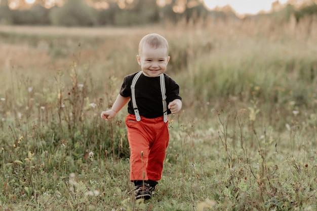 Śliczna mała chłopiec ono uśmiecha się w jesieni polu