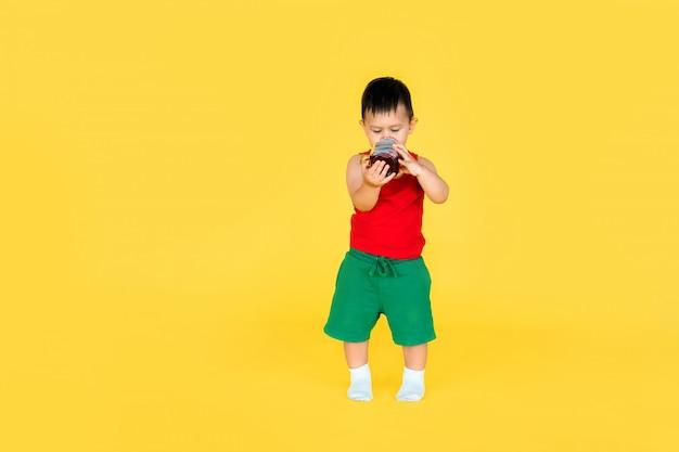 Śliczna mała chłopiec w czerwonej koszulce i zieleni krótkim z filiżanką sok na kolorze żółtym