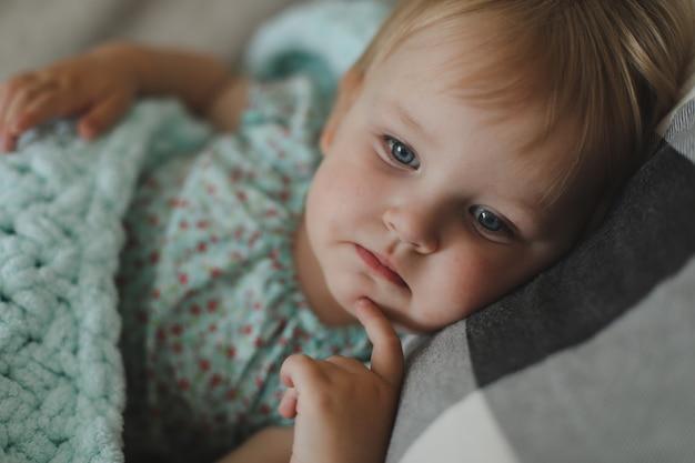 Śliczna mała dwuletnia dziewczynka leżąca pod pledem w domu