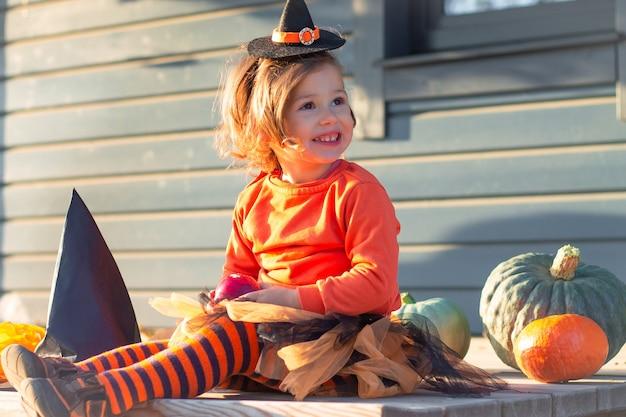 Śliczna mała dziewczynka 2-3 w pomarańczowo-czarnym stroju wiedźmy siedzi obok dyń na tarasie drewnianego szarego domu