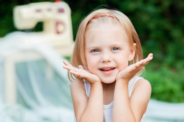 Śliczna mała dziewczynka 3 lat, portret na tle maszyny do szycia