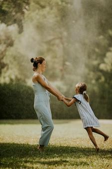 Śliczna mała dziewczynka bawi się na trawie z matką